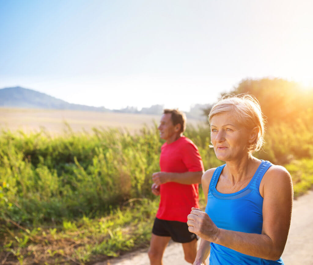 older couple jogging outside in warm weather